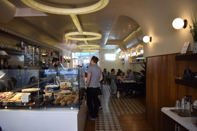 Interior of Gossip Coffee with pastry display, bar, and customers in line to order