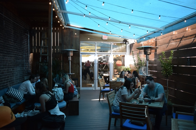 Outdoor patio with string lights, bright blue awning, and seated patrons drinking coffee at Gossip Coffee