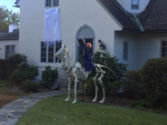 "A house in Sleepy Hollow decorated for Halloween, with a ghost hanging form the window and a skeleton horse mounted by a ""horseman"" with a pumpkin for a head."
