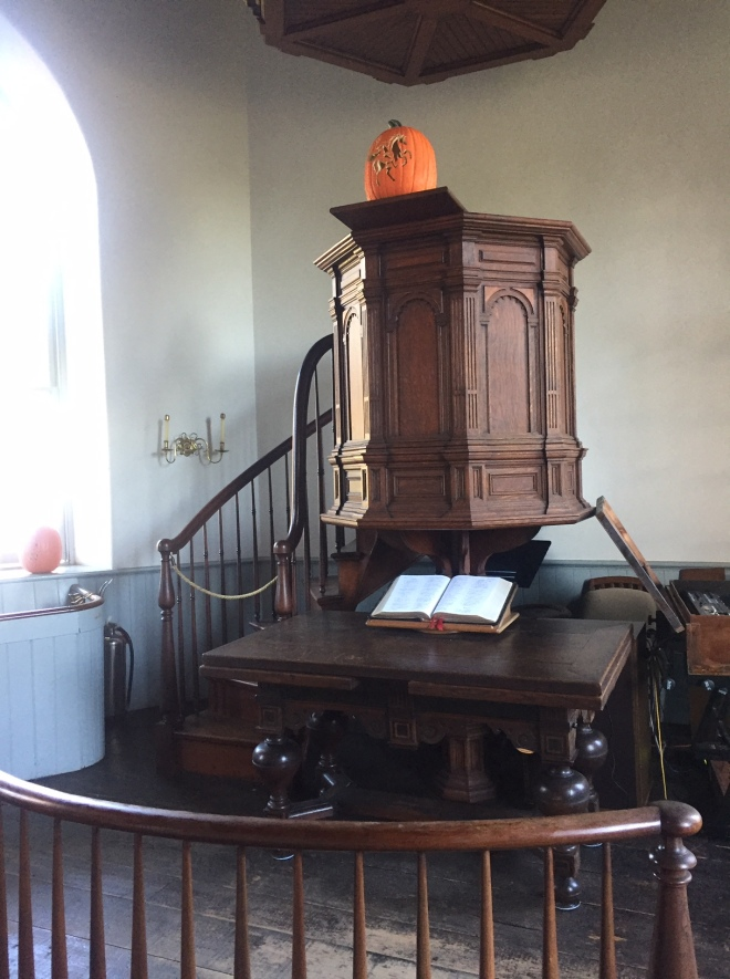 Interior of Old Dutch Church in Sleepy Hollow, NY with pulpit, chandelier, organ, and carved pumpkins for Halloween