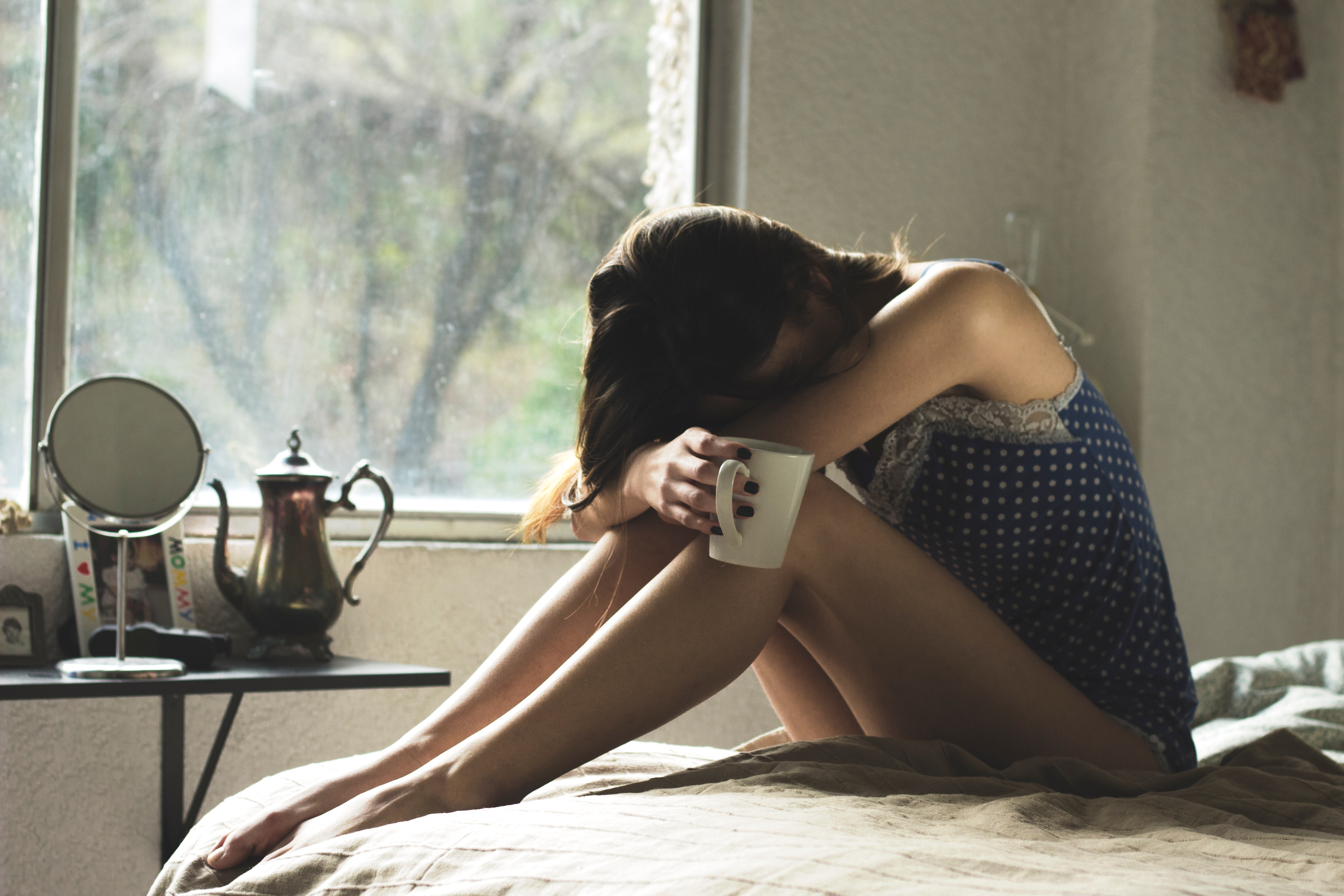woman with migraine hunches over on bed, holds coffee cup