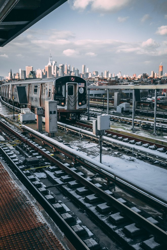 new york city subway on cold, snow day, f train, with manhattan in the background